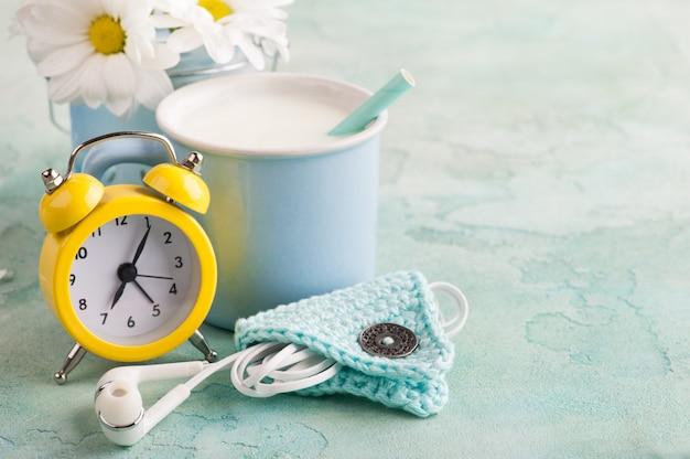 Een beker melk met koptelefoon en een klok