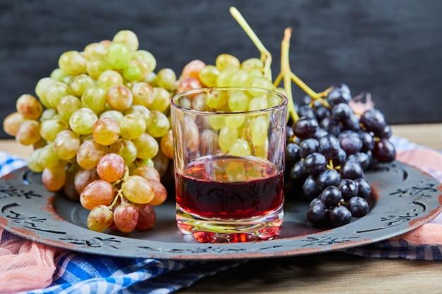 Een beker wijn met druiventrossen eromheen.