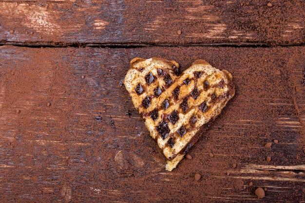 Een belgische hartvormige wafel met chocolade op houten achtergrond. plat leggen. kopieer ruimte