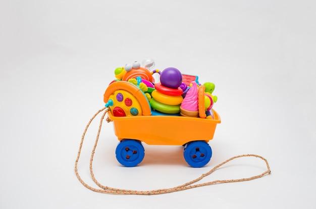 Een berg speelgoed op een kar. kleurrijk speelgoed zit in de winkelwagen. veel speelgoed op een witte ruimte. vrije ruimte. de wagen is oranje.