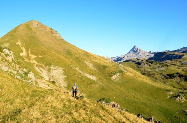 Een bergbeklimmer loopt richting de bergen arlas en anie in de pyreneeën van frankrijk
