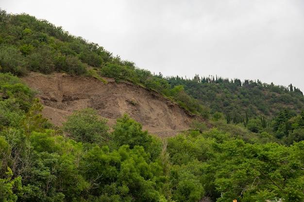Een bergverschuiving in een ecologisch gevaarlijke zone, de val van grote lagen aarde die de weg blokkeren. bodem onder erosieomstandigheden.