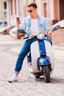 Een bericht aan een vriend typen. knappe jonge man zittend op scooter en kijken naar zijn mobiele telefoon