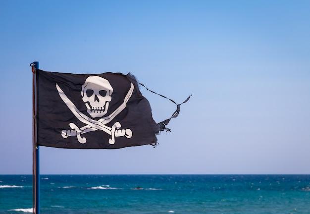 Een beschadigde piratenvlag tijdens een sterke winderige dag, met copyspace