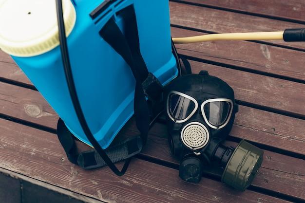 Een beschermend masker en knapzak voor desinfectie liggen op een bankje