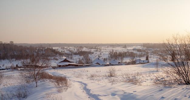 Een besneeuwd dorp met huizen en een brede weg ernaartoe. er ligt veel sneeuw in de velden en de daken van de huizen steken nauwelijks uit de sneeuw