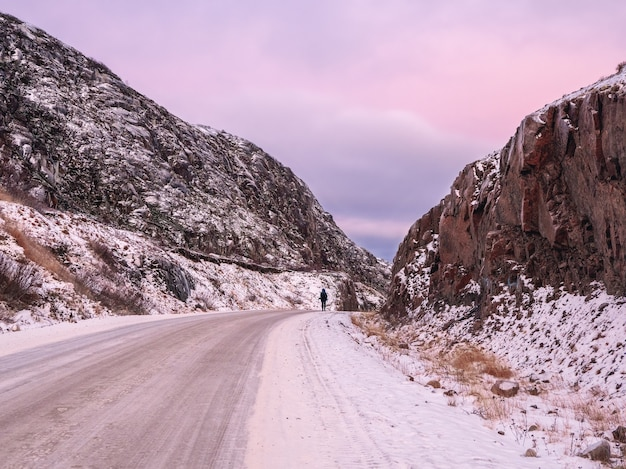 Een besneeuwde weg die zich uitstrekt in de verte tussen de heuvels. kola-schiereiland. de magische paarse kleur van de dageraad.