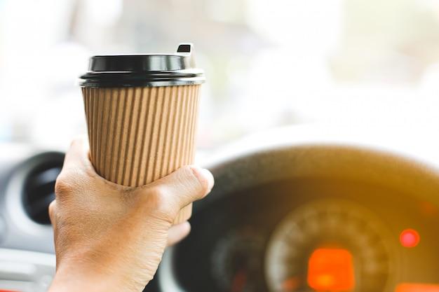 Een bestuurder die koffie in de auto drinkt.
