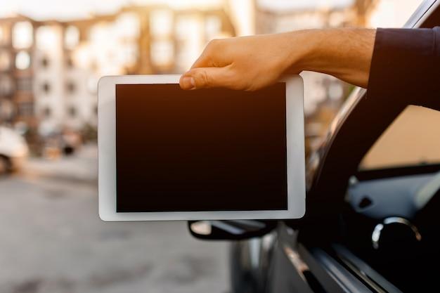 Een bestuurder toont een close-up van een tablet-pc-scherm in de camera. lege ruimte voor uw tekst of afbeeldingen.