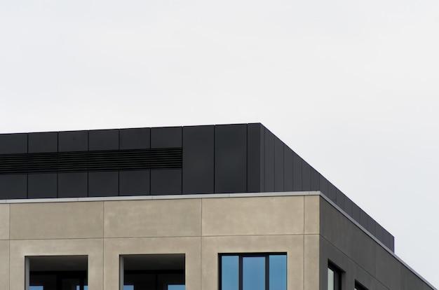 Een betonnen gebouw met spiegelvensters onder de heldere hemel