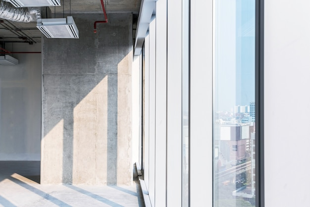 Een betonnen zuil met zonlicht aangegoten tijdens de binnenrenovatie met open plafondsysteemwerk. lege ruimte voor investeringen van ontwikkelaars.