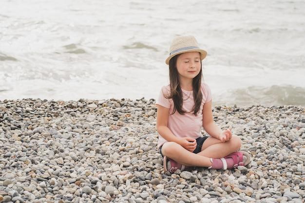 Een bewust meisje mediteert aan de kust bij de zee een klein meisje doet yoga psychologische rijping ...