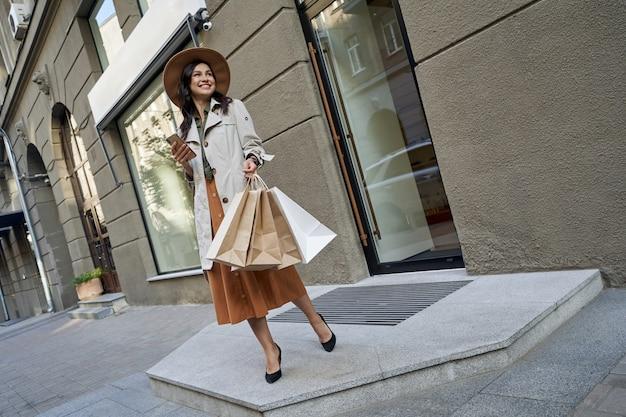 Een bezoek aan een modeboetiek over de volledige lengte van een jonge charmante modieuze vrouw met boodschappentassen in de hand