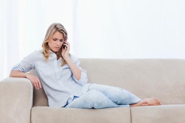 Een bezorgd uitziende vrouw liggend op een bank is praten over haar mobiele telefoon