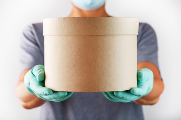 Een bezorger in rubberen handschoenen en een masker houdt het pakket vast.