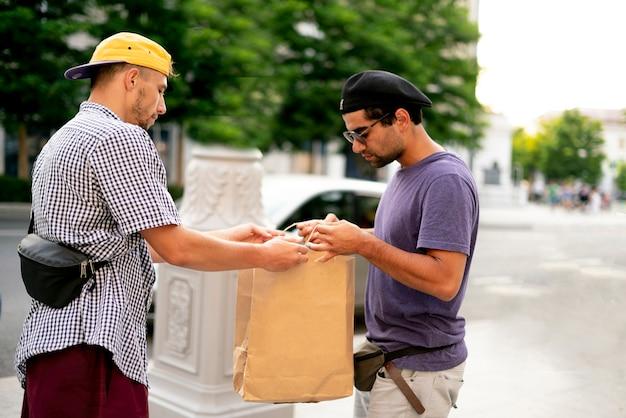Een bezorging van de voedselzak van de koerier, pakketbezorgservice