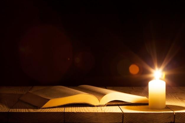 Een bijbel op de tafel in het licht van een kaars