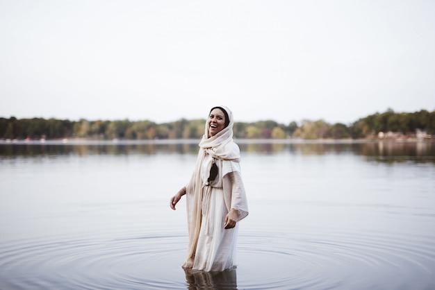 Een bijbelse gewaad dragen en vrouw die terwijl status in het water lachen
