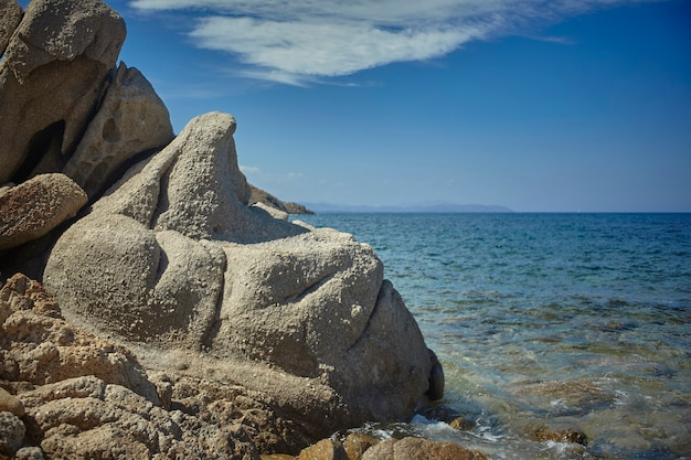Een bijzondere rots met bochtige en golvende vormen met de achtergrond van de azuurblauwe en kristallijne