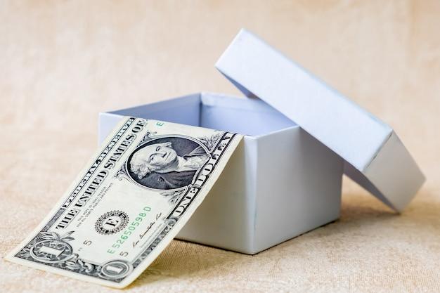 Een biljet van een amerikaanse dollar in witte geschenkdoos