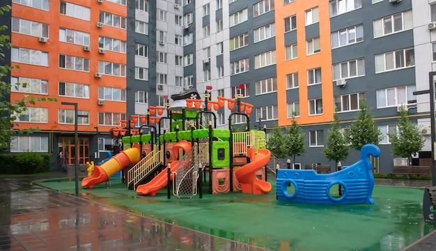 Een binnenplaats van hoogbouw met een nieuwe moderne kleurrijke en grote speeltuin op een regenachtige zomerdag zonder mensen. lege buitenspeeltuin. een plek voor kinderspelletjes en sport.