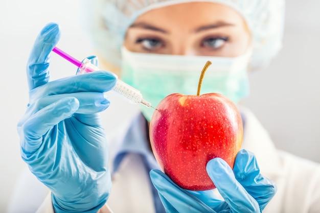 Een biologe-vrouw modificeert een appel genetisch voor een langer leven vrouwelijke onderzoeker of wetenschapper met...