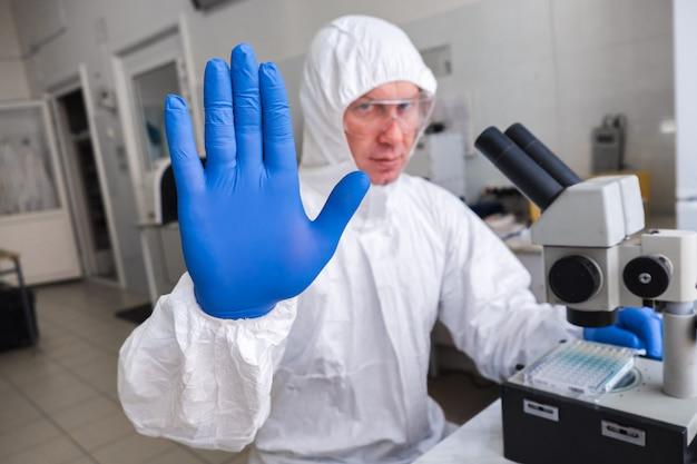 Een bioloog in een wit beschermend pak en bril werkt met een microscoop in het laboratorium. het concept van een epidemie en een pandemie. handgebaar - stop