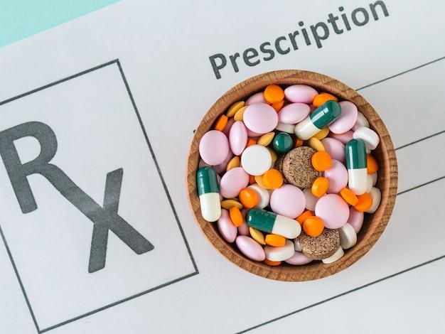 Een blad met het voorschrift van een arts en een houten kom met pillen op een blauwe tafel.