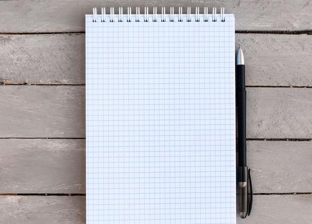 Een blanco notitieblok in een vak voor vermeldingen op een houten tafel