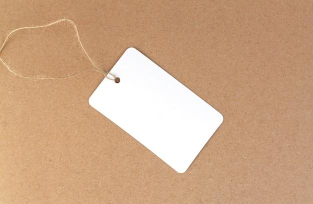 Een blanco stoffen label of prijskaartje op bruine achtergrond
