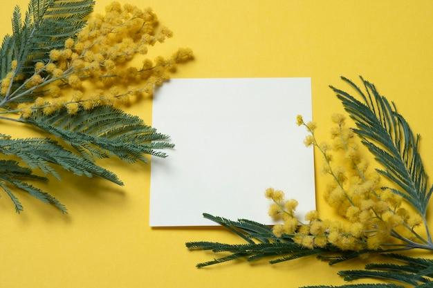 Een blanco vel papier op een gele achtergrond met takjes mimosa.