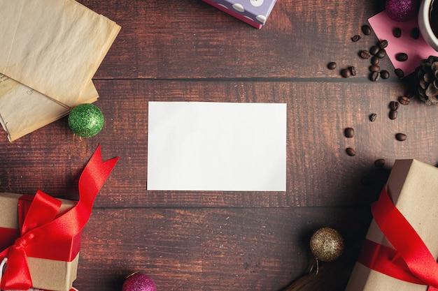Een blanco wit papier en geschenkdozen op houten vloer