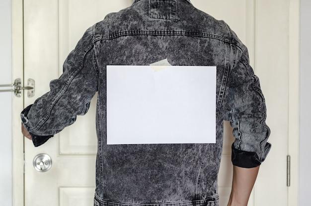 Een blanco witte notitie met plakband op de rug van de man