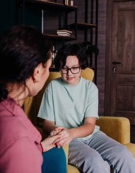 Een blank tienermeisje zit in een stoel in een kamer bij een receptie met een vrouwelijke psycholoog