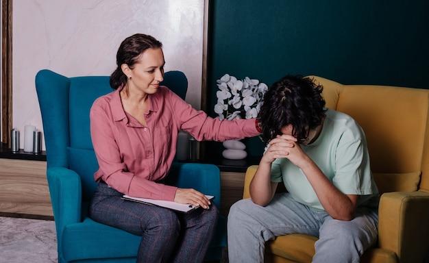 Een blank tienermeisje zit in een stoel op kantoor bij een receptie met een vrouwelijke psycholoog