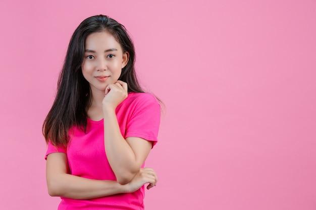 Een blanke aziatische vrouw legt haar linkerhand tegen haar kin op een roze.