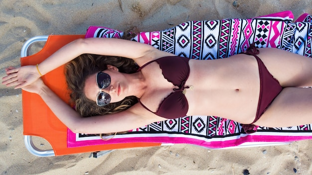 Een blanke blonde vrouw in zonnebril en bordeauxrode zwembroek