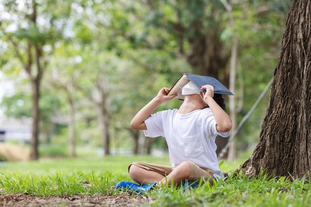 Een blanke jongen met een hygiënisch masker zit alleen onder een boom en leest een boek dat zijn hoofd bedekt.