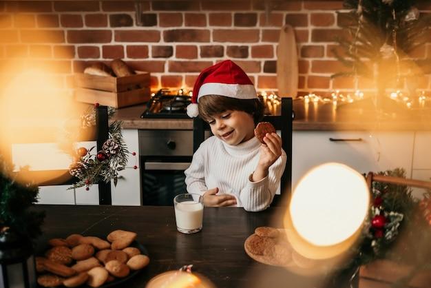 Een blanke jongen zit aan de keukentafel in een witte trui en een rode kerstmuts met melk en koekjes
