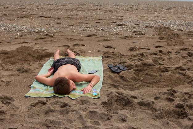 Een blanke man die overdag op een handdoek op een strand ligt