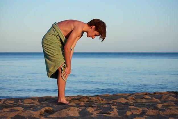 Een blanke man die zichzelf afdroogt met een groene handdoek op een strand met een zee op de achtergrond