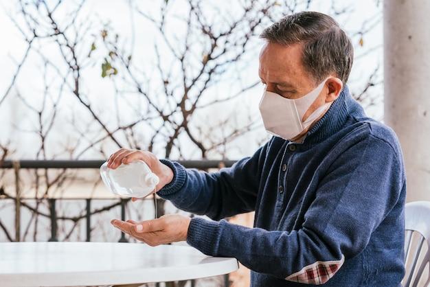 Een blanke man in een medisch masker met behulp van een handdesinfecterend middel
