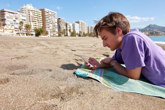 Een blanke man liggend op een handdoek op een strand die overdag zijn telefoon checkt