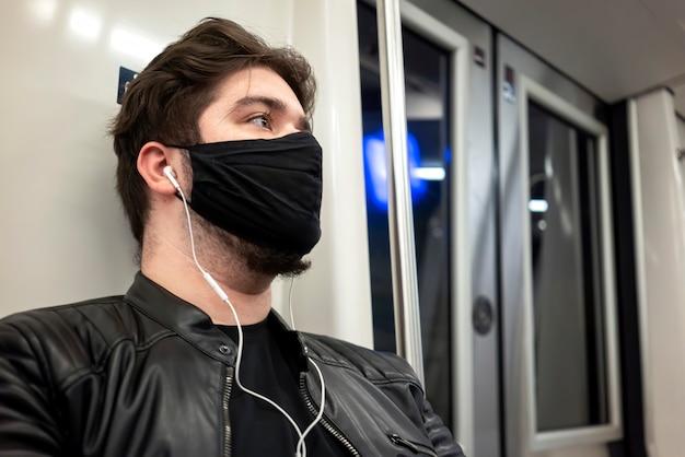 Een blanke man met baard en koptelefoon in zwart medisch masker in de metro