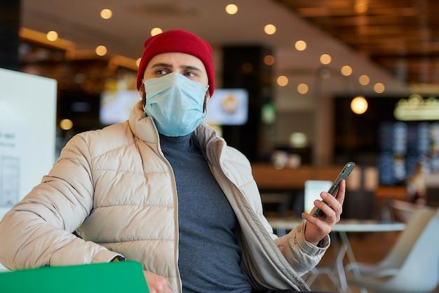 Een blanke man met een chirurgisch masker op het gezicht met behulp van een smartphone in het winkelcentrum.