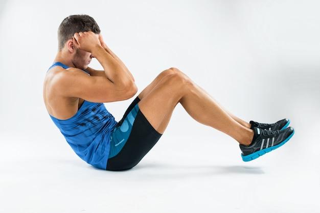Een blanke man oefenen crunches fitness gewichten oefeningen in studio.