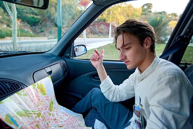 Een blanke man uit spanje zit in zijn auto en kijkt naar een papieren kaart - toerisme en reizen