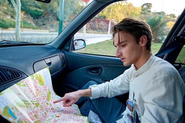 Een blanke man uit spanje zit in zijn auto en wijst naar een papieren kaart - toerisme en reizen