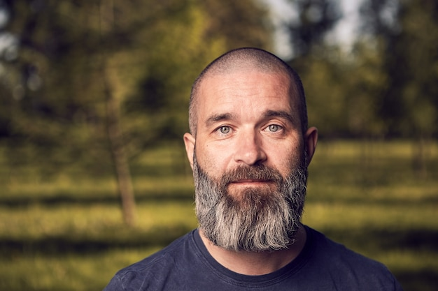 Een blanke man van ongeveer 43 jaar oud met kort haar en baard heeft een rust in een park, close-up.