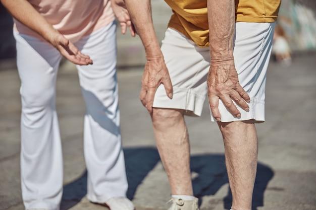 Een blanke mannelijke gepensioneerde die zich naar haar man buigt en lijdt aan gewrichtspijn